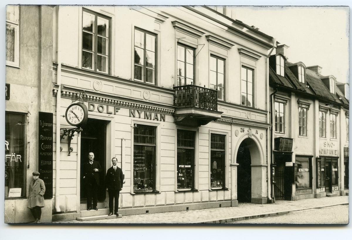 Nymans ur.  Urfabrikören Adolf Nyman och hans son Göran Adolf Nyman framför affären, Stora gatan 26 a, 1920-talet.  Kv. Lennart i Västerås.