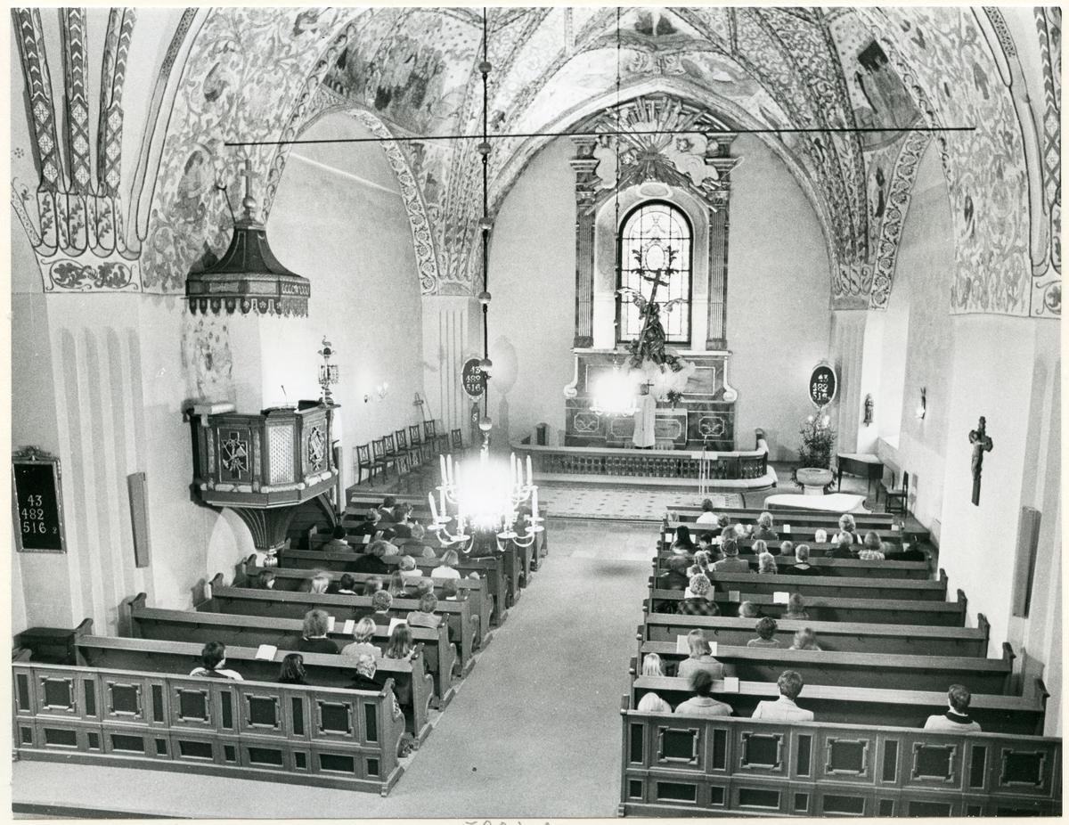 Dingtuna sn, kyrkan.  Gudstjänst i Dingtuna kyrka. Åhörarna sitter i kyrkbänkarna och prästen står vid altaret.