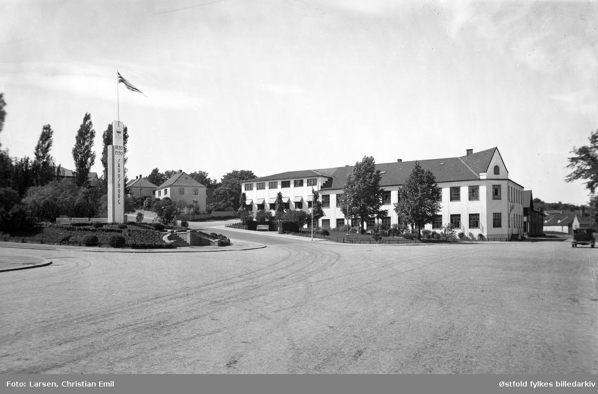Eksteriør av fabrikklokalene til SEFA i Sarpsborg, Sarpsborg Elektriske Fabrikker. Produsent av Sarpsborgkomfyren. Til venstre  Jernbaneparken med reklame fra byjubileet i Sarpsborg 1839-1939.