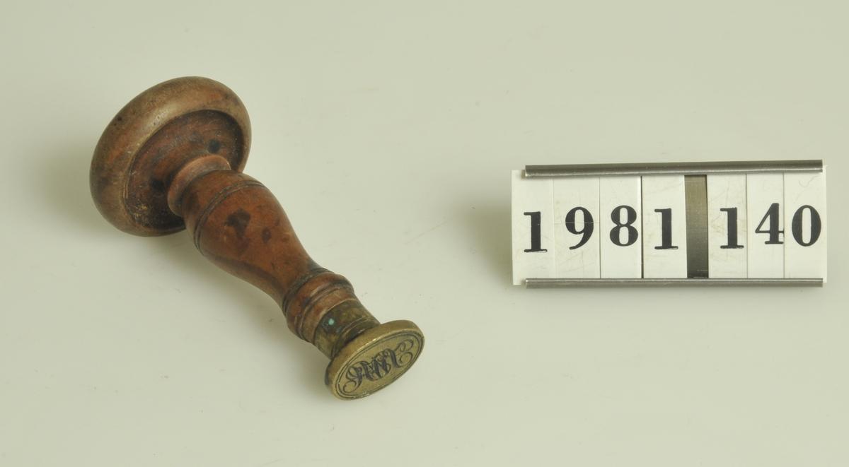Av mässing med initialerna IWH. Svarvat träskaft.