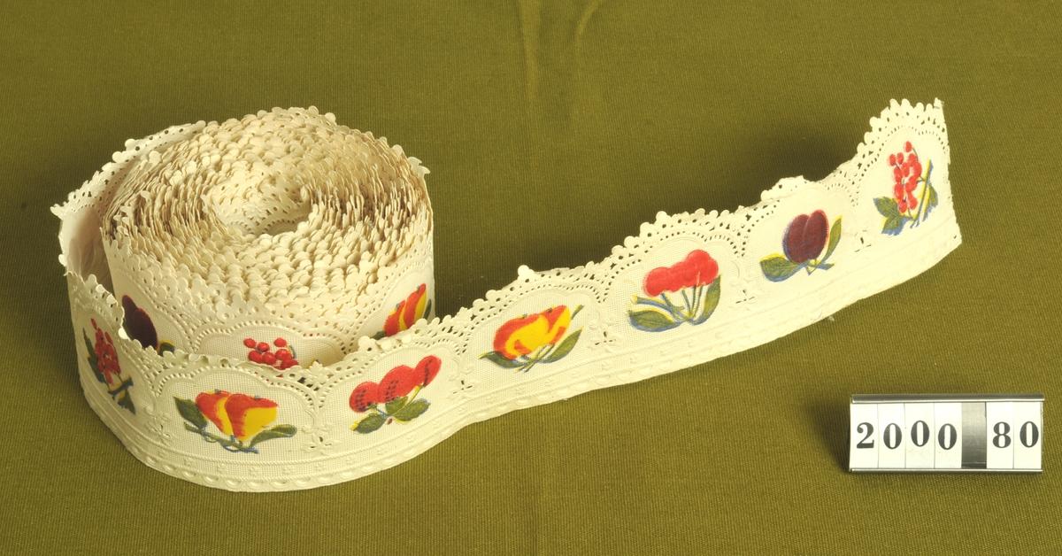 Präglat mönster i form av bär och frukter, kolorerade mot vit botten.