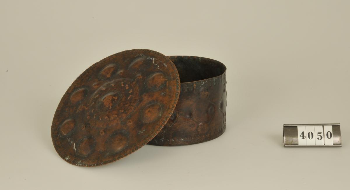 Med lock. Med driven, punsad och graverad dekor. På ena sidan initialerna BH anno 1614, på undersidan AAS 1751. Rund.
