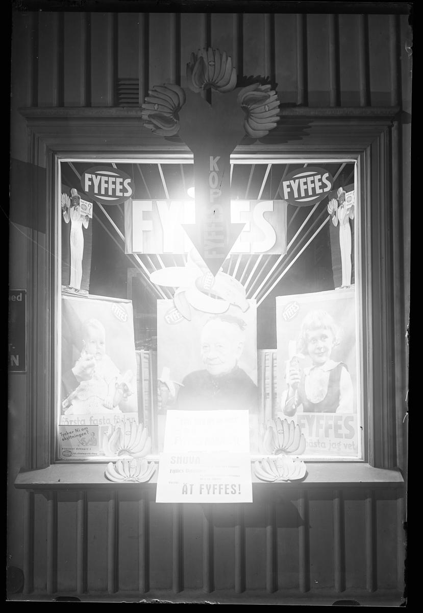 """Ett upplyst skyltfönster med reklam för Fyffes bananer. I fotografens anteckningar står det """"Köhlers affär""""."""