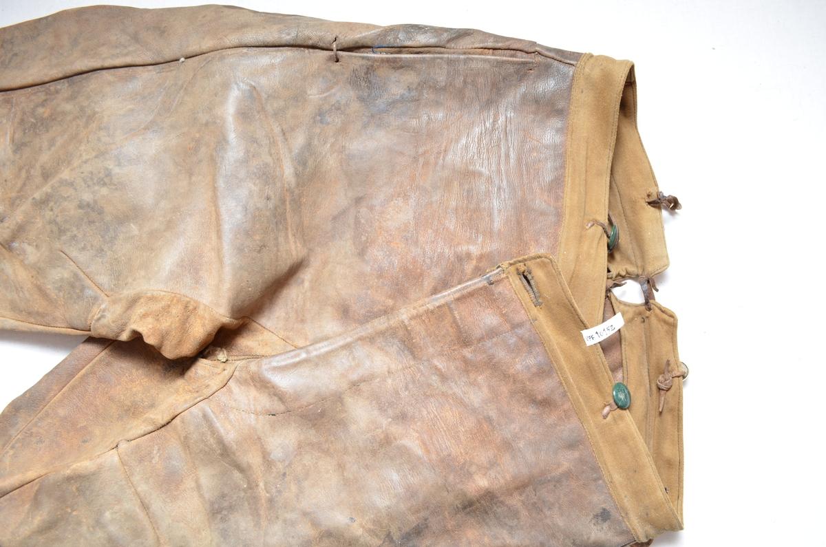 Brun skinnbrok (langbrok). Nedre del av buksebeina er i brunt bomulltøy. (26 cm). (Kan det ha vore kortbrok tidlegare? ) Linning og for i gylfen er i same bomullstøyet.To stikklommer framme  med blått bomullstøy på innsida. Gylf. Open saum midt bak (7 cm), hekta saman med ei skinnreim. Forskjellige knappar.
