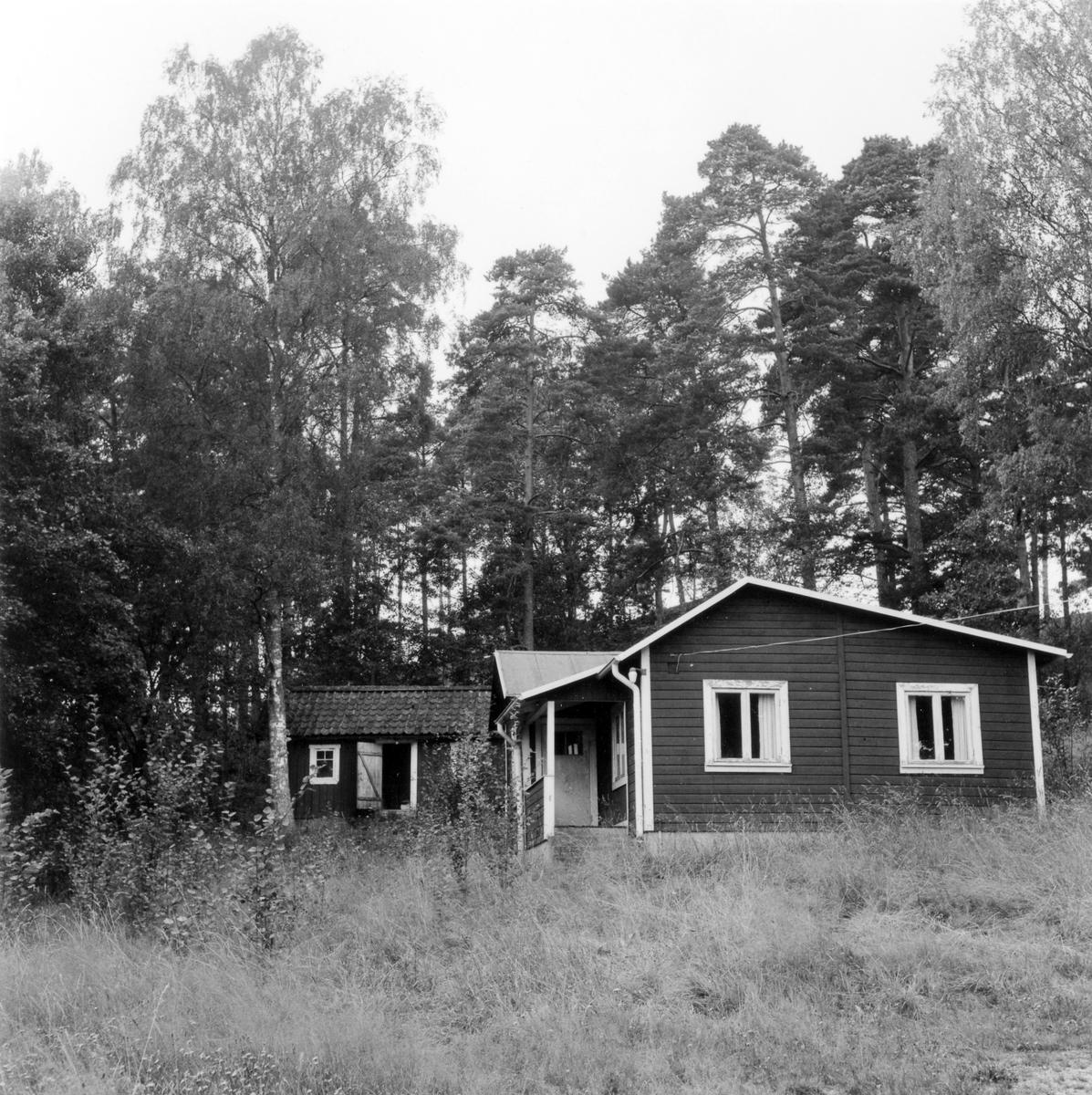 Ett mindre bostadshus och uthus i en liten träddunge.  Rödmålat uthus och mindre bostadshus beläget intill barnhemmet Solstrand. Byggnaderna revs augusti 1978.