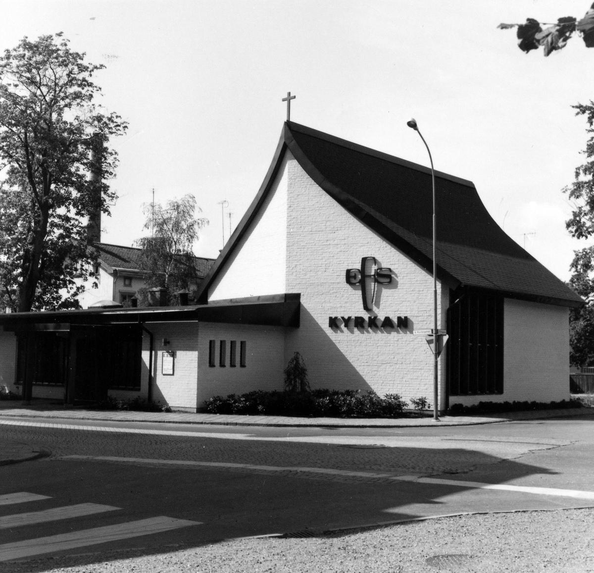 EFS nya kyrka. Kyrkan är vit med mörkt tak och texten EFS KYRKAN skriven på husväggen.