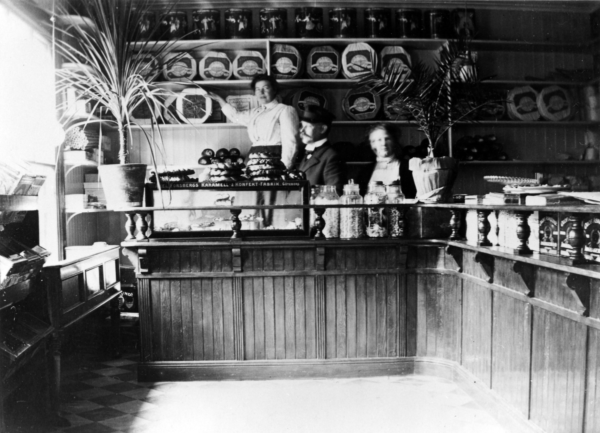 Bakom disken på K.P. Wessmans speceriaffär står 2 kvinnor och en man. På disken finns bland annat kakor och konfektyrer av all dess slag samt 2 stora krukväxter. Kvarteret Storken 6.