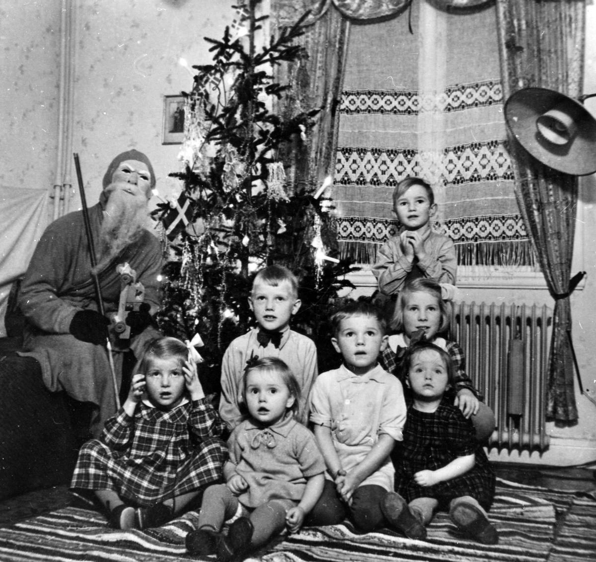 En liten skara barn sitter framför en julgran och en man utklädd till tomte sitter till vänster i bild. Olof Jacobsen och en grupp barn hos familjen Bolin, Nolby.