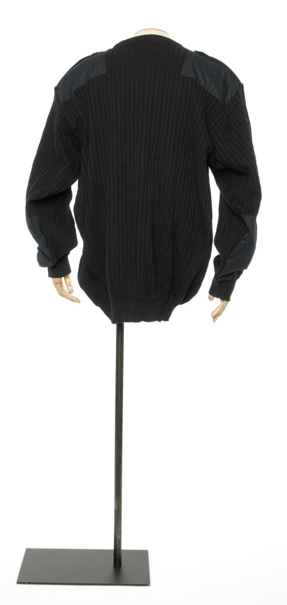 7595d6ba Mørkblå genser i strikket ull med tillsatt lapper av antatt syntetisk stoff  på armene og skuldrene