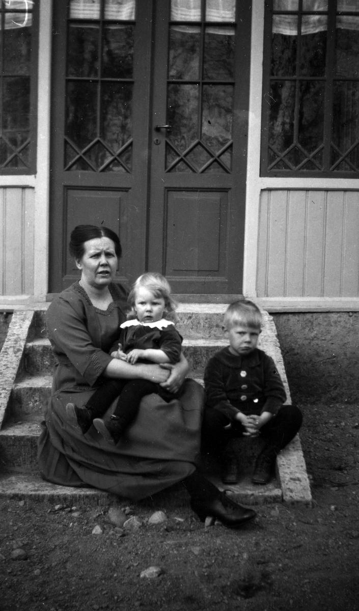 En kvinna och två barn sitter på en trappa vid en ytterdörr.