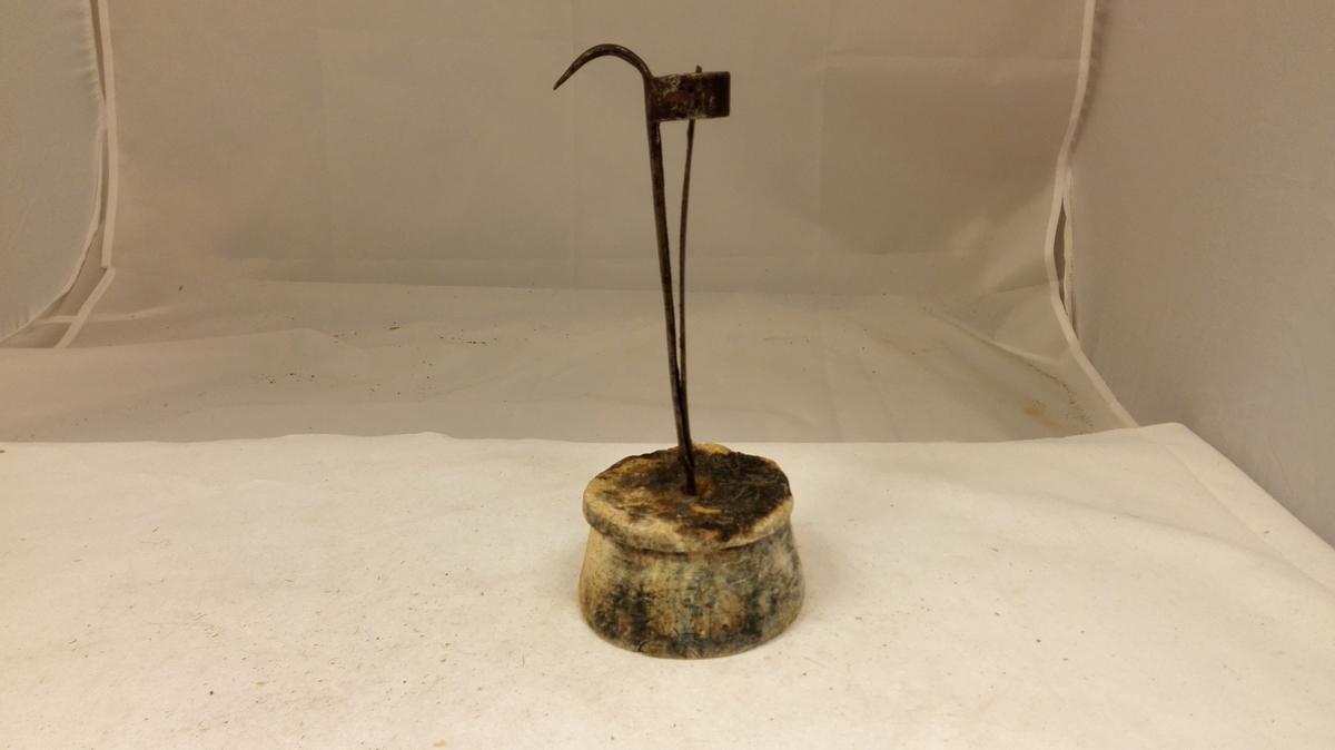 Lysestake.  Lysestake. I en rundspikket, 5 cm höi, nedre diameter 9,5 - 9,7, bjerketræsfot er innsat en lyseholder av jern, 16,7 cm höi. Til lyseholderen er klinket en fjær av stål og er der i ringens övre kant utsmidd en krok til å hænge staken efter.  Gave fra farver Jakob Steen, Hafslo