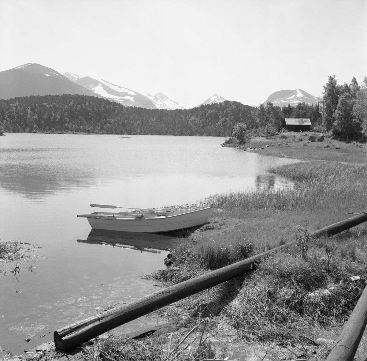 Motiv av en båt ved Mausavatnet. I bakgrunnen står et telt