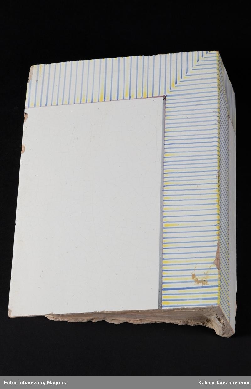 """KLM 38947. Kakel. Till kakelugn. Vit tennglasyr på gulröd lergodsskärv. Dekormålad i koboltblå och antimongult. Drejad rump. Stänk av blyglasyr på några av kakelns baksidor. Märkt med stort X på rumpen.  Förteckning över samtliga kakel, med mått inom parentes, gjord i samband med inventering 1997:   :1. 5 st. fasadkakel, plana         (32,5x23x6 cm) :2. 4 st. hörnfasad, plana         (32x26x11,5 cm)     1 st.  -""""-                              (32x15x6 cm)     1 st.  -""""-                              (32x10x5 cm)     1 st.  -""""-                              (20x13x6 cm) fragment :3. 4 st. fasadkakel, välvda       (32,5x26,5x7 cm)     1 st.  -""""-           1/2 lod       (32,5x11,5x7 cm) :4. 4 st. fotsims, plana             (7x25x7 cm) fragment :5. 5 st. fotsims, plana             (14x25x4 cm) :6. 1 st. krönkakel, välvda        (10x26x9 cm) :7. 1 st. fotsims, hörn              (10x21x7 cm) :8. 4 st. fragment"""