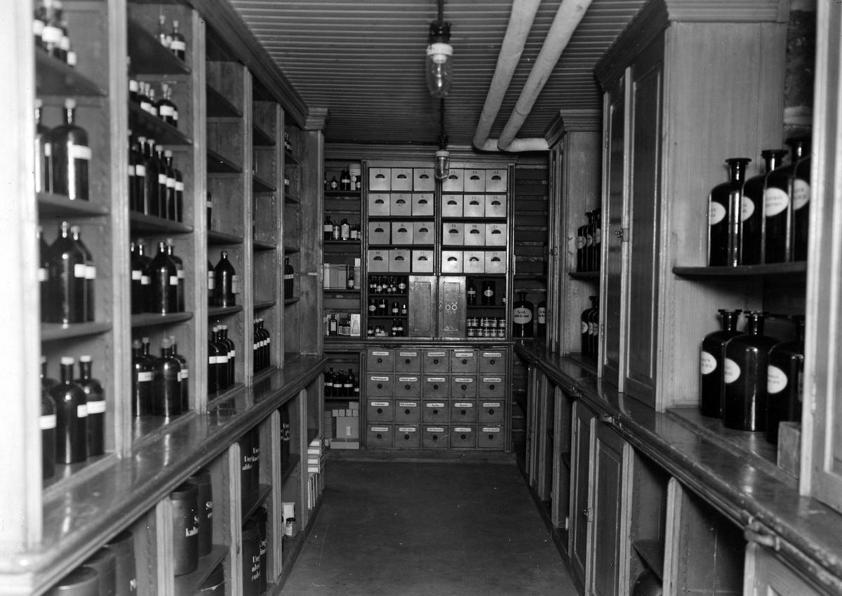 Bilden medicinalkällaren på apoteket Hjorten. Väggana ärr fylld från golv till tak med hyllor innehållande glasflaskor och lådor.