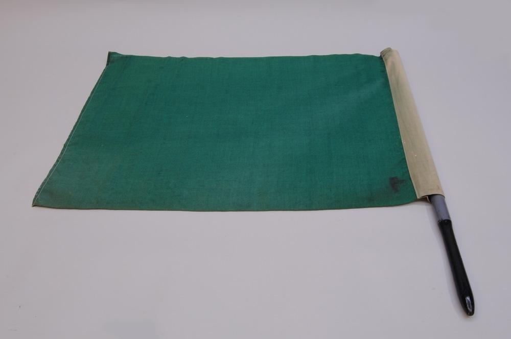 Grön signalflagga i fodral av gråbrungrönt målat kompositmaterial, med hållare av läder. Flaggan har ett skaft av svarvat, gråmålat trä med svart handtag. Fodralet har fack för två flaggor, den röda saknas.  Jvm 23001:1 Flagga Jvm 23001:2 Handtag Jvm 23001:3 Fodral