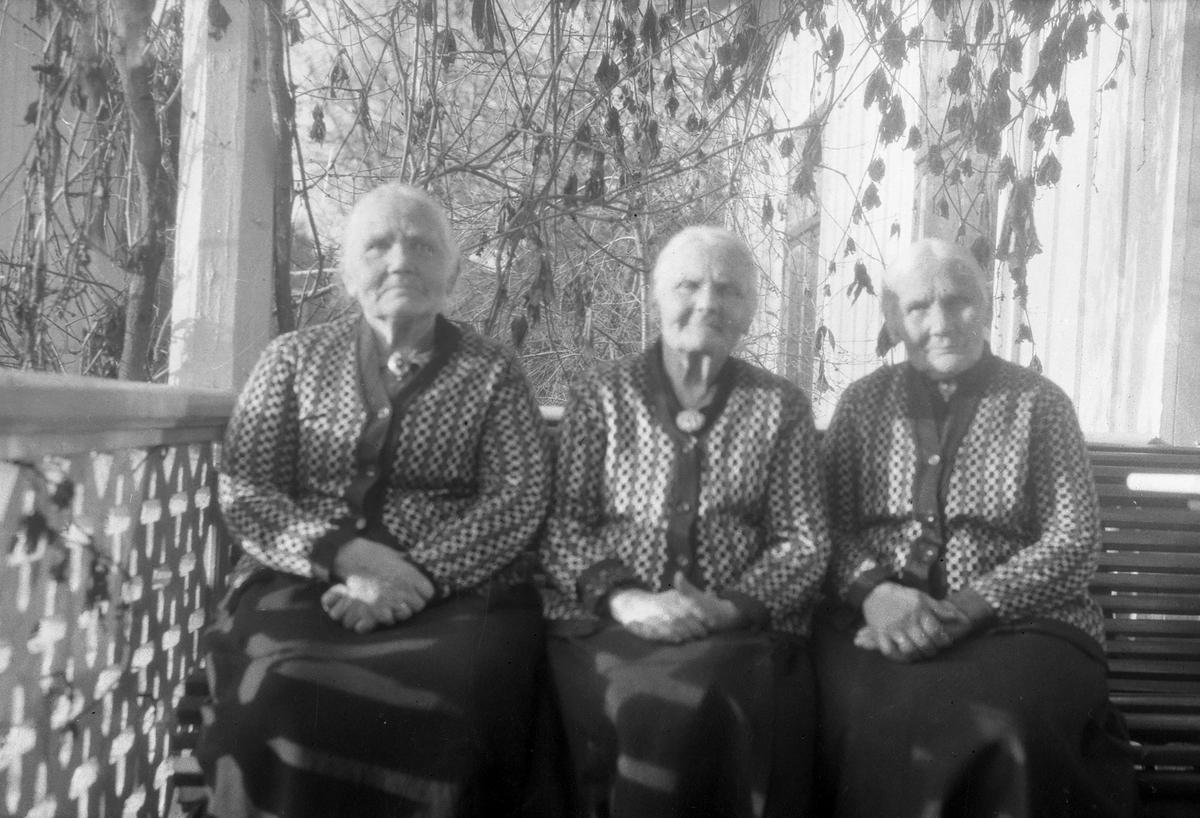 Tre eldre kvinner,likt kledd.
