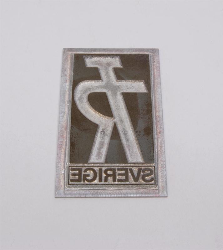 """Rektangulär kliché av grå metall. Mitt på finns en rektangulär upphöjning, i den finns Trafikrestaurangers logotyp med bokstäverna """"TR"""" sammanlänkade i form av """"TR-pojken"""". Logotypen är präglad. Den kallas TR-pojken eftersom det ser ut som en person som håller armen i en serveringsgest. Under logotypen finns texten: """"SERVICE"""" i relief."""