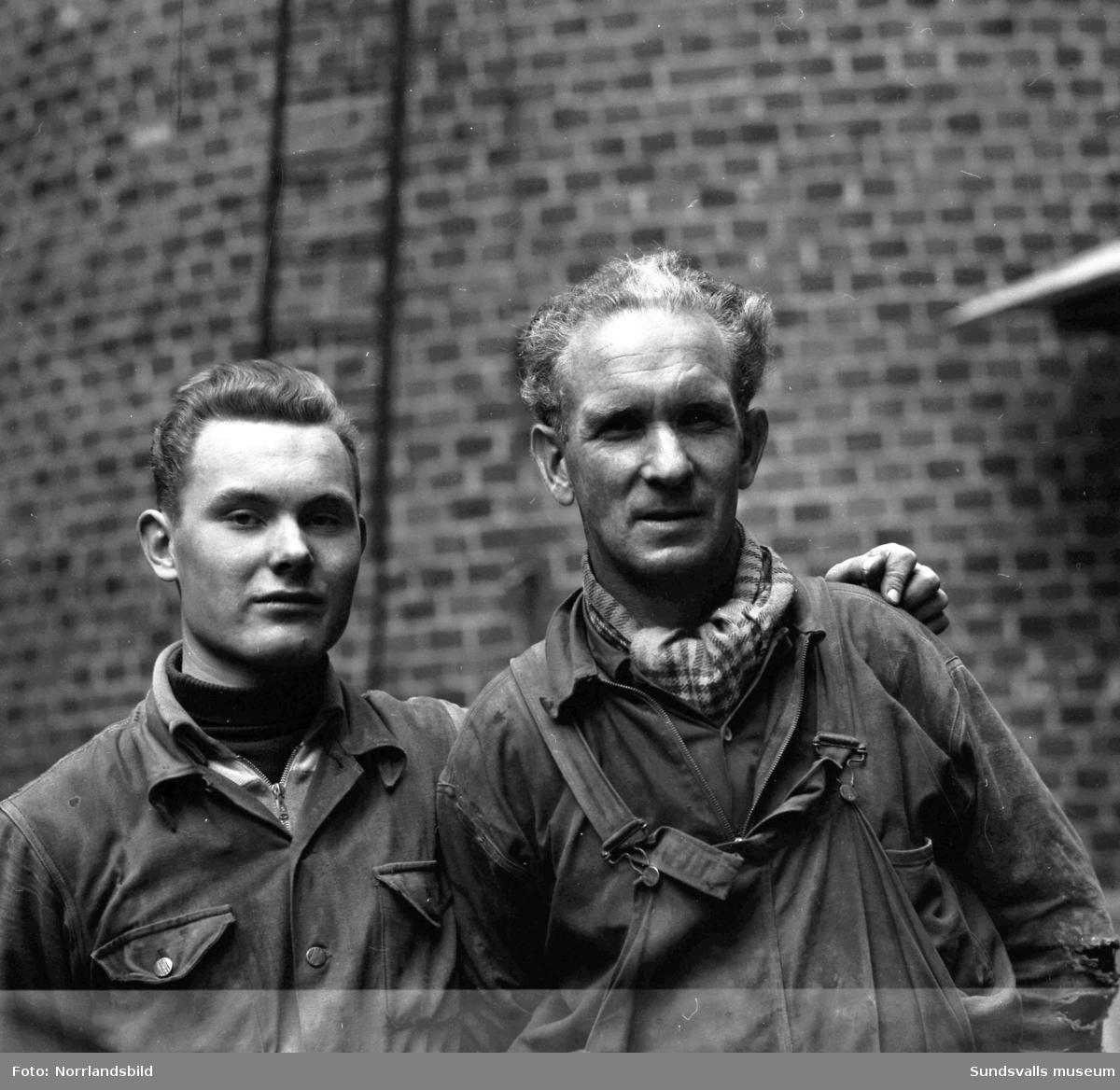 Två män vid Östrandsfabrikens skorsten.