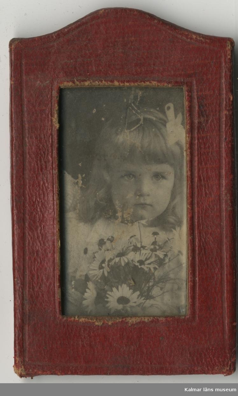 En flicka som har en blombukett med prästkragar framför sig.