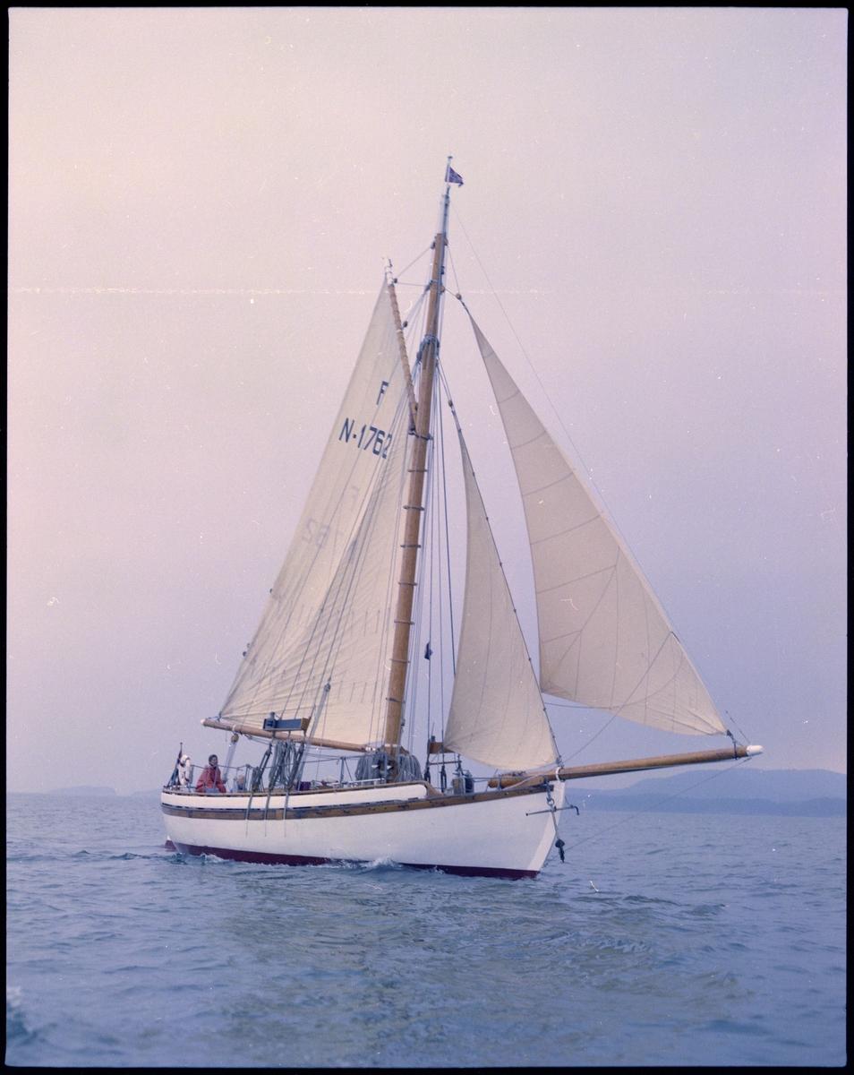 """Seilskøyta """"Heidrun"""" på sjøen. To personer sitter ombord."""