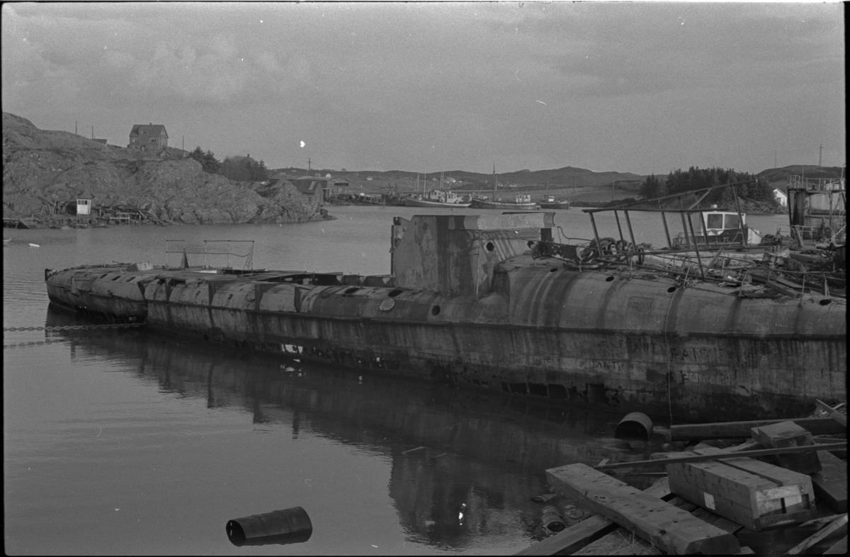 Vraket av et fartøy, muligens en torpedojager ligger ved Karmsund verft. Det er mye søppel rundt.