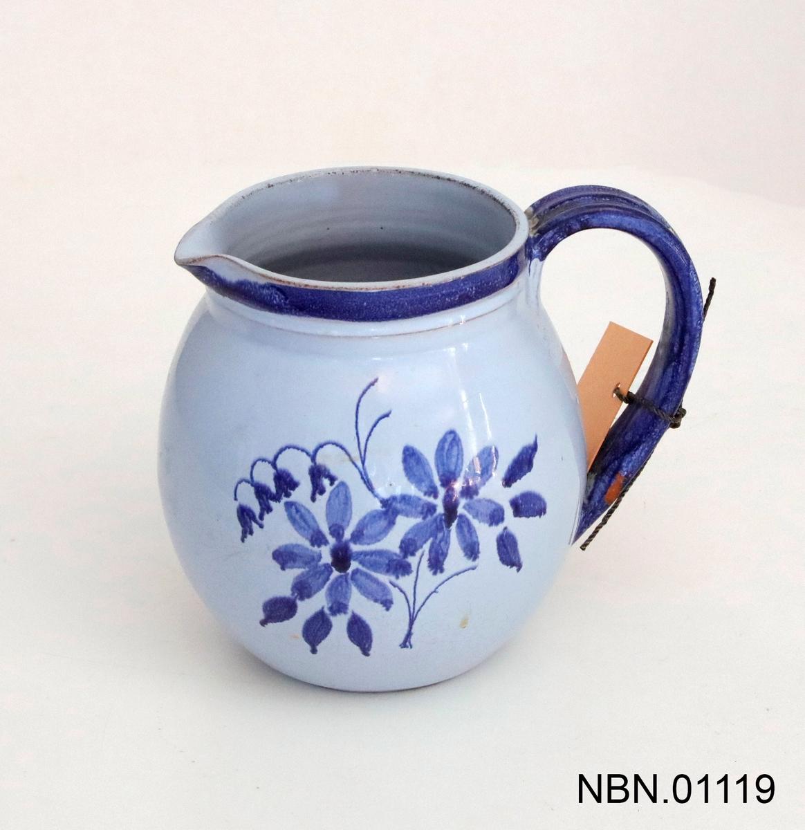 Mugge, blåmalt glasert keramikk med blomsterdekor. Hank med riller. Rundt form.