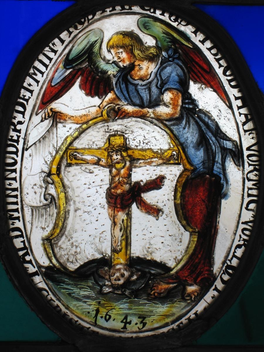 Kristus på korset i et prikket skjold, holdes av engel i blått og brunt, litt grønt på vingene.  Tekst rundt  feltet