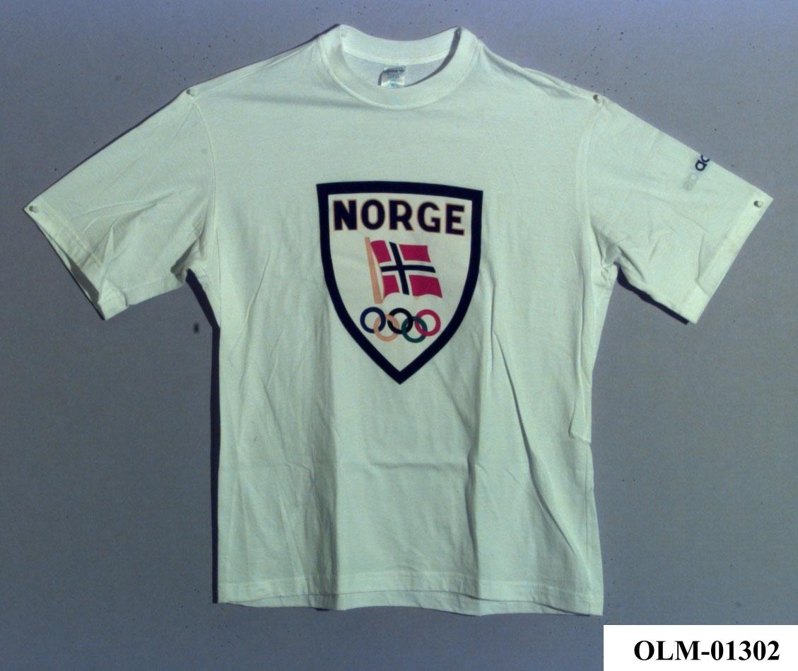 T-skjorte med våpenskjold på brystet, med tekst NORGE, norsk flagg og olympiske ringer