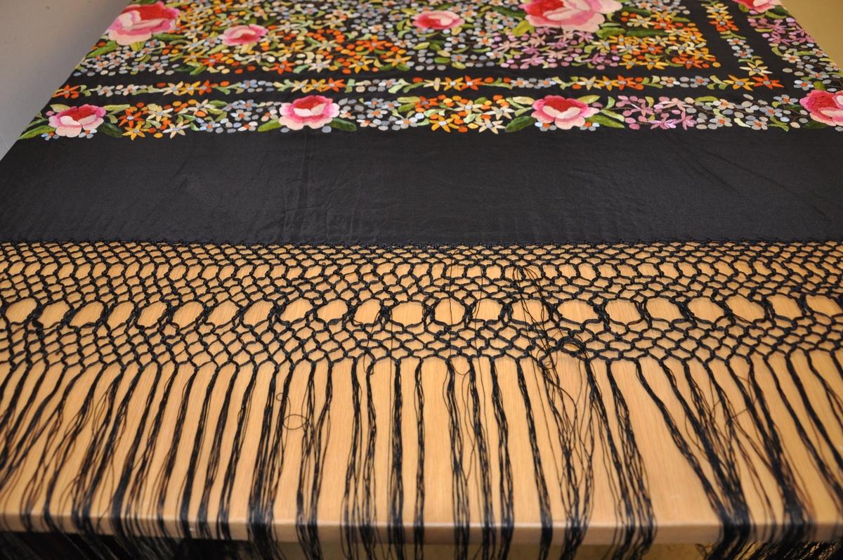 Svart flygelteppe av silke. På midten er det en firkant og to border brodert dekor med motiv av blomster. Rundt teppet er det en kniplet borde med hengene tråder.