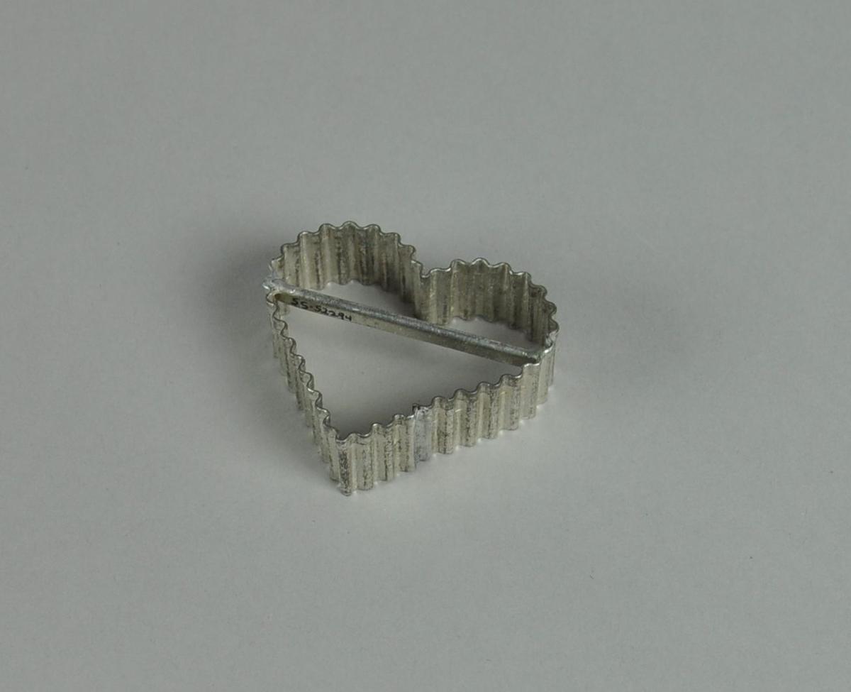 Kakeform av aluminium. Hjerteform med bølgete profil og hank på midten.