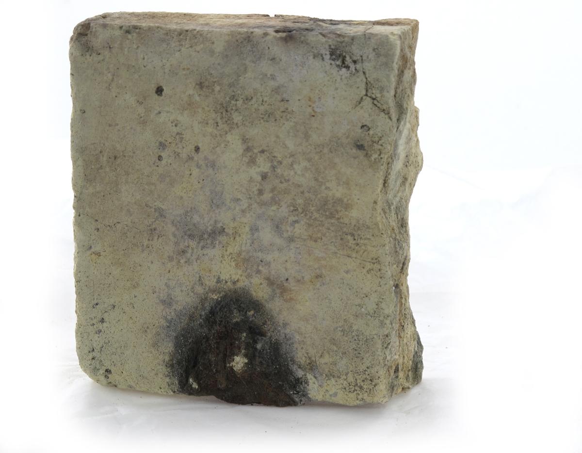 """Teglstein fra slaveskipet """"Fredensborg. Tilnærmet halv stein, med et stort sort hull på en kant."""