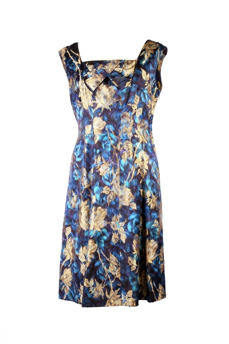Mønstret kjole uten ermer, med drapering ved utringningen og glidelås i siden.