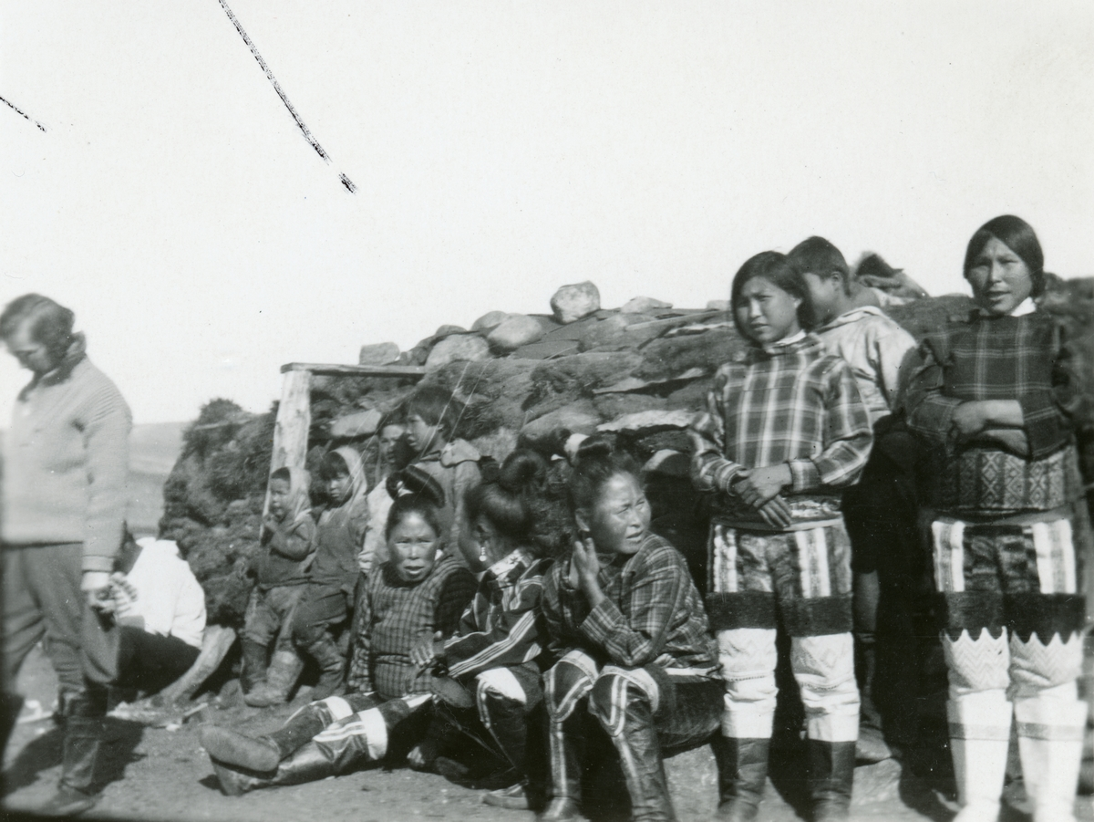 To grønlandske kvinner i sine folkedrakter poserer foran et hus.