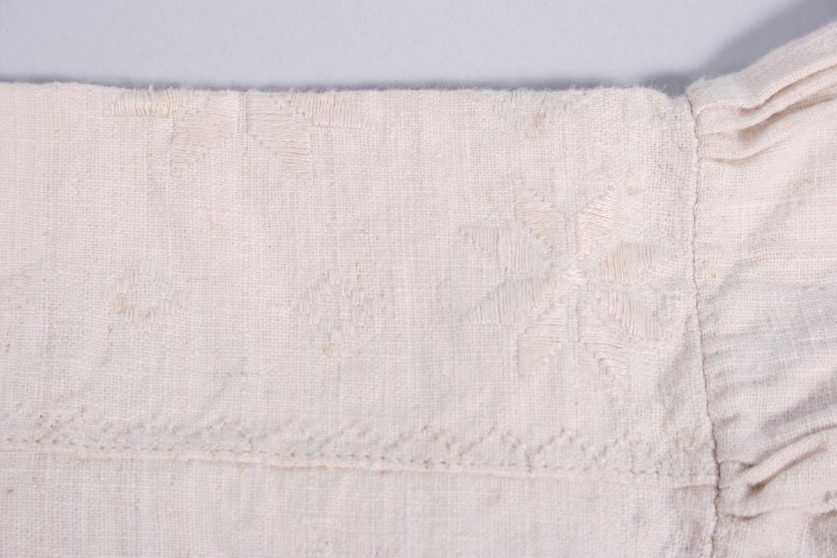 Plagget er av to typer lin, fin lin i overdelen og grovere i nedre del. Serken har bærestykke med hvitsømsbroderi m.bl. åttebladsrose. I halsrigningen er stoffet brettet innover og det er laget en løpegang med knyttebånd. Splitt i halsrigningen . Den er forsterket med en regels i nedre del. Under splitten er det brodert åttebladsrose, initialer, årstall og dekor. Serken er sydd sammen ved midjehøyde. Bakstykket består av forskjellige kvaliteter. I sidene er det felt inn kiler. Ermene er sydd til med små legg både til fram og bakstykket og på toppen av skulderpartiet. Spjeld ved ermhulen. Ermene er tett rynket til ermlinningene. Nederst på ermene er det bomullsstoff som er rynket til ermlinningene.