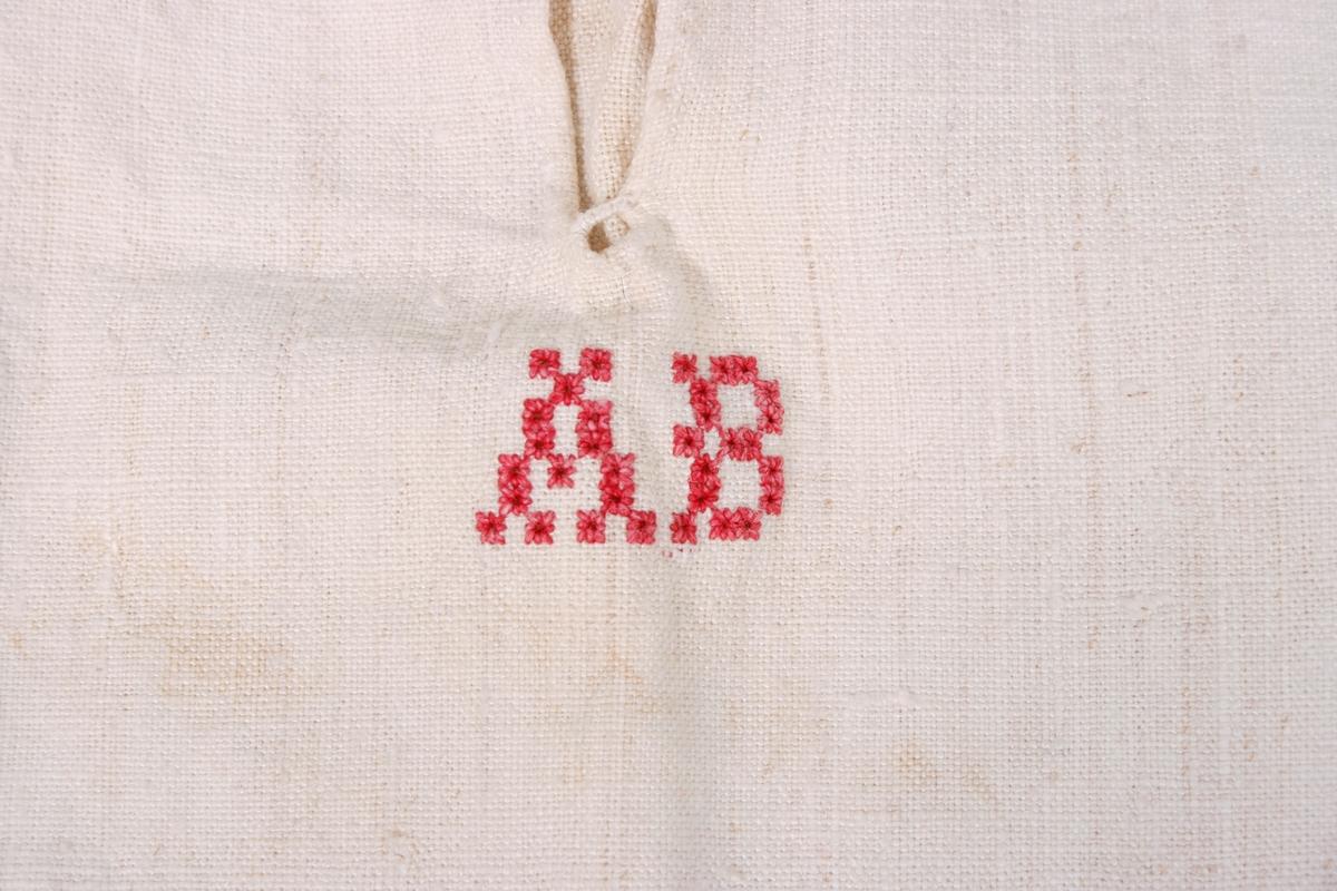 Skjorten har stående krave med 2 knapphull og stikning i nedre kant. Bærestykke over skuldrene med kiler som er rynket mot kraven. Kilene og bærestykket har stikninger. Splitten MF er forsterket med en regels nederst. Under splitten initialer brodert med hullsting. Splitter i sidene som er forsterket med firkanter som er brettet til trekanter. Ermene er sydd i med 3 legg mot framstykket og 3 legg mot bakstykket. Isydde spjeld under armhulen. Ermene er tett rynket til mot mansjettene.  Mansjettene har 2 håndsydde knapphull, stikninger og musetagger ytterst.
