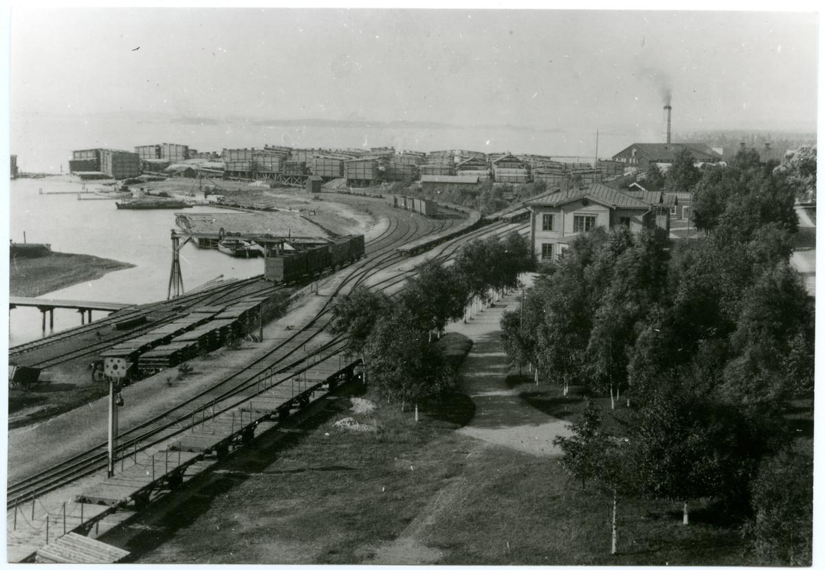 Korsnäs station samt sågverk vid sjön Runn. Stationshuset syns bland träden och bortanför syns såghuset med brädgården till vänster.
