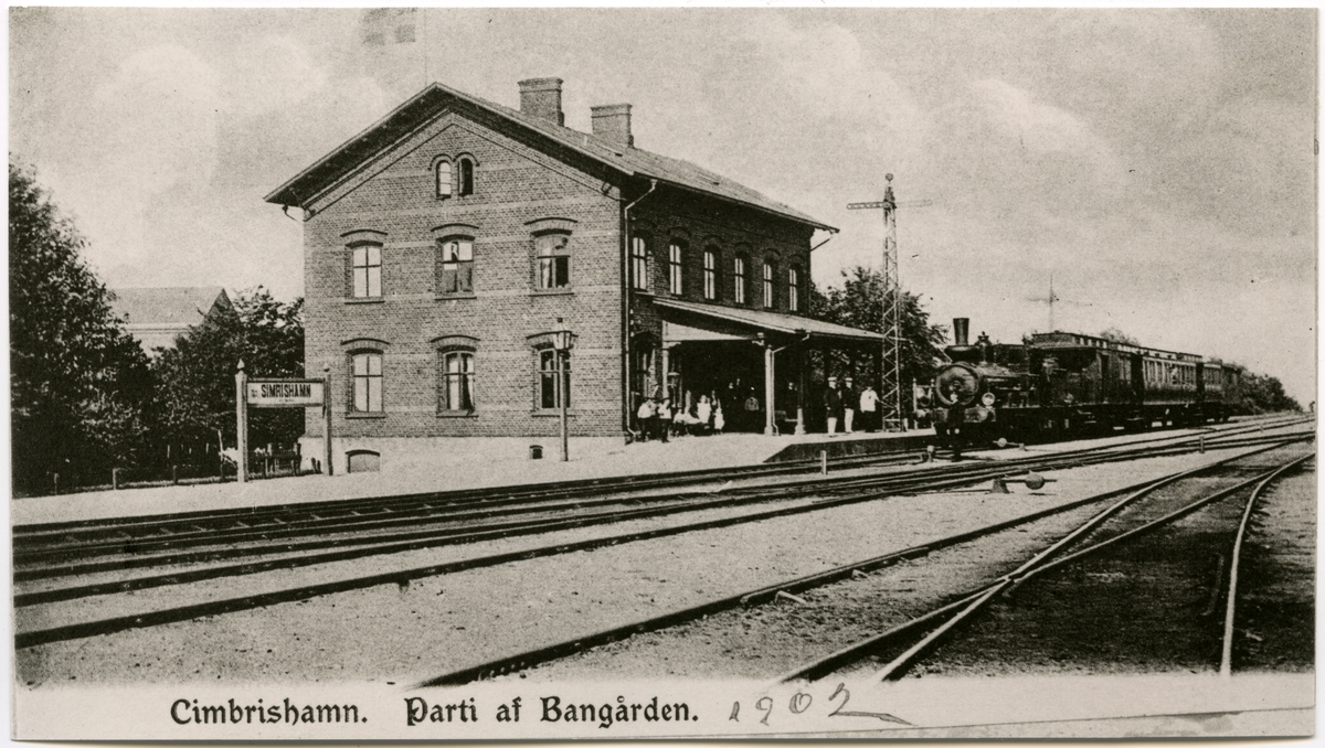 Simrishamns bangård och stationshus med ångtåg.