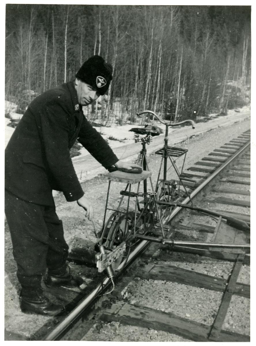 Banvakt Pettersson demonstrerar egentillverkad rälssmörjningsapparat efter linjen mellan Selsjön - Aspeå.