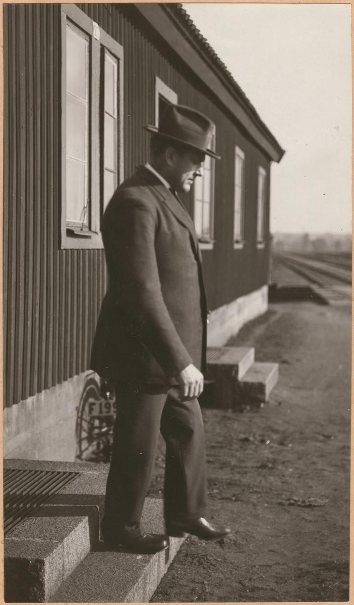 """Fotografi från """"Redogörelse för tillverkning vid Statens Järnvägars protesverkstad i Nässjö"""", 1932. Man med dubbla benproteser går nedför trappa utan stöd."""