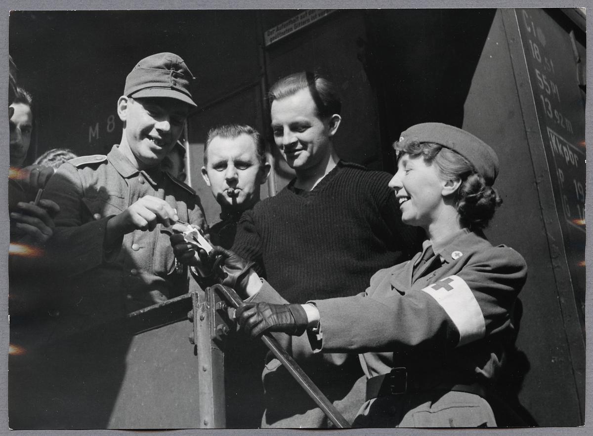 Rödakorssyster överlämnar cigaretter till sårade tyska soldater ombord på ett tyskt sjukvårdståg i Hallsberg under Andra Världskriget.