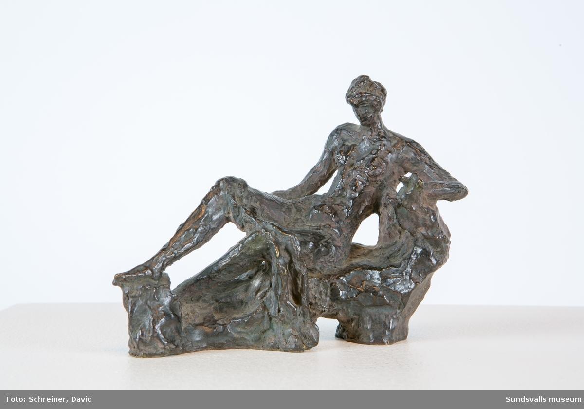 En liggande kvinna som stödjer sig på den högra armen. Hon har en handduk draperad över benen.