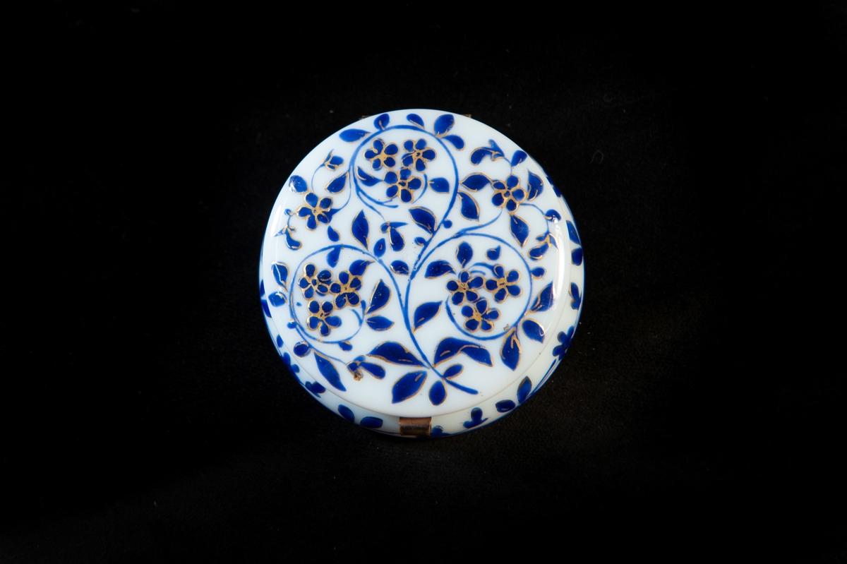 Rund dosa i ljusblått opalglas med tät dekor av blomslingor i mörkblått och guld. Metallskoning av koppar runt locket.