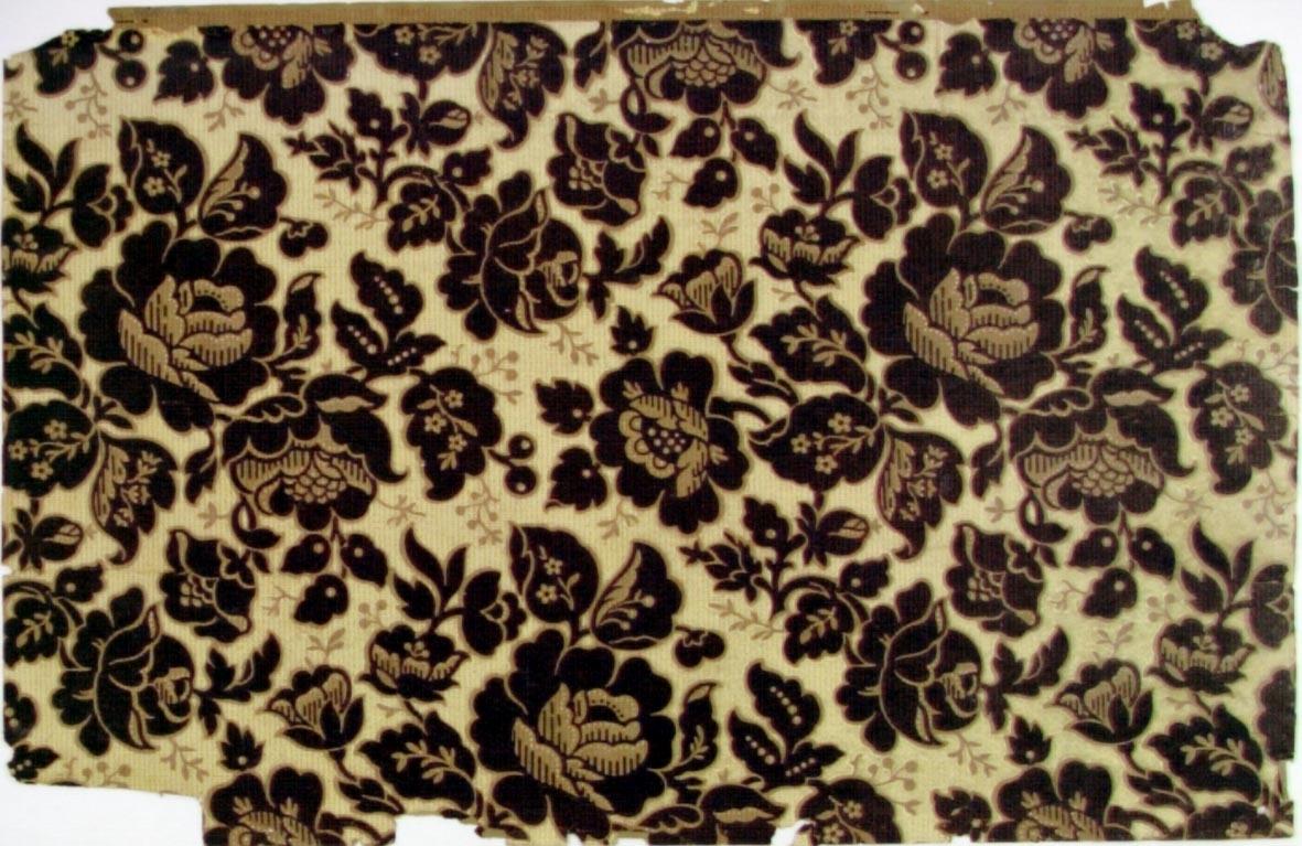 Tätt ytfyllande blommönster. Gulbrunt genomfärgat papper med tryck i svart på en citrongul bakgrund. Övertryck med rött prick-/streckmönster. Nybarock