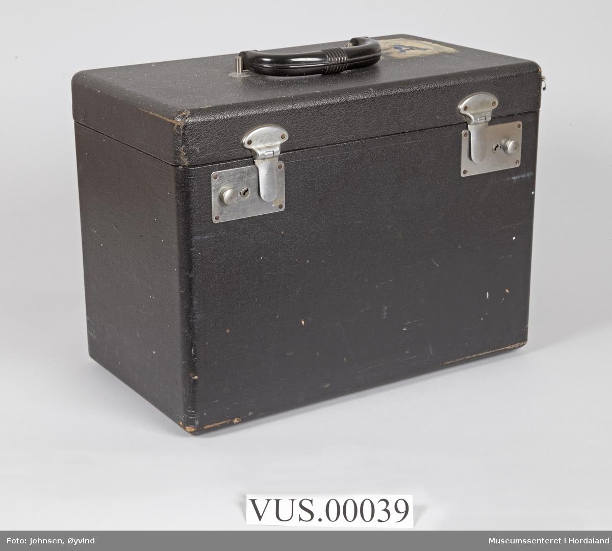 Komplett symaskin med diverse utstyr i svart kasse. I bruksanvisning står Singer Featherweight 221 K Portable Sewing Machine.