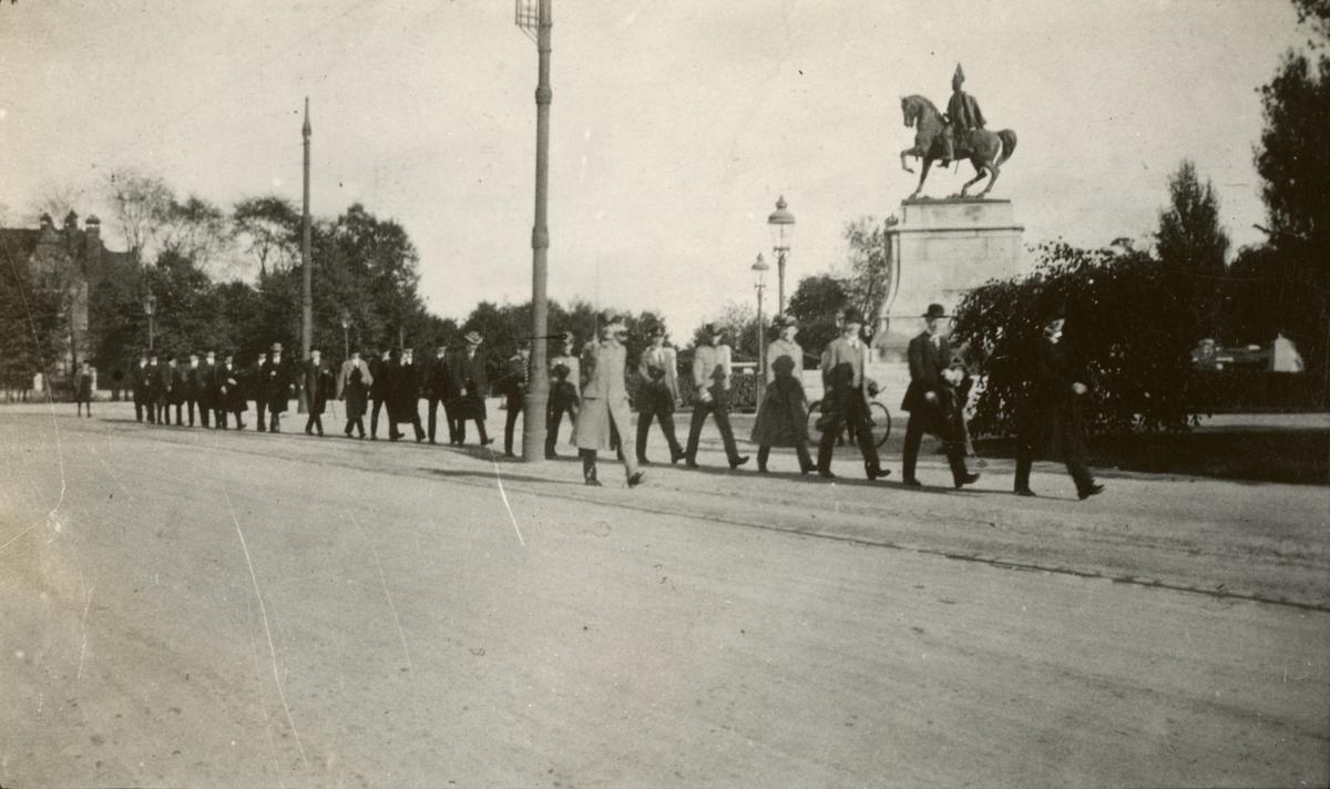 Soldater från Göta livgarde I 2 och civilpersoner på marsch på Djurgården.