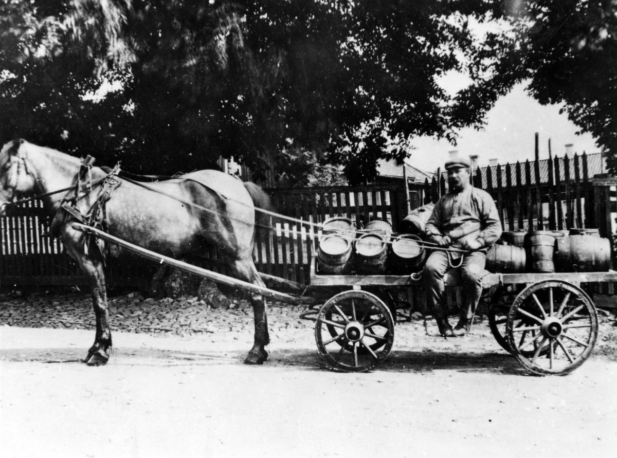 """Johan """"Dreckejohan"""" Olsson, anställd på Alingsås Bryggeri AB, sitter på en hästvagn med öltunnor på flaket."""