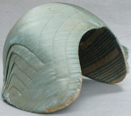 Hedemoramössa?Bindmössa i ljusblå Foder av (blekt gammal)Fodrad med blå/naturvit randigt bomullstyg. Då mössan är trasig i kanterna, kan man se att stommen är gjord på traditionellt sätt med papp och lintov. Ett handgjort band av lin  i nacken.