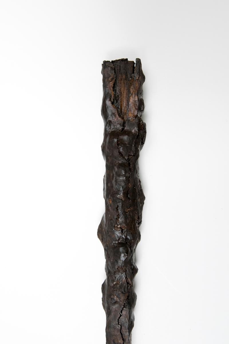 Yxformat redskap av järn, skaft även trä. Yxbladet har konvex eggsida, halsen är smal, och nacken är fyrsidig, något nedåtböjd och avsmalnande i en spets. Yxbladets ena sida har en korsformad stämpel (likarmat kors). Yxskaftet är fyrsidigt, bredast nedtill.