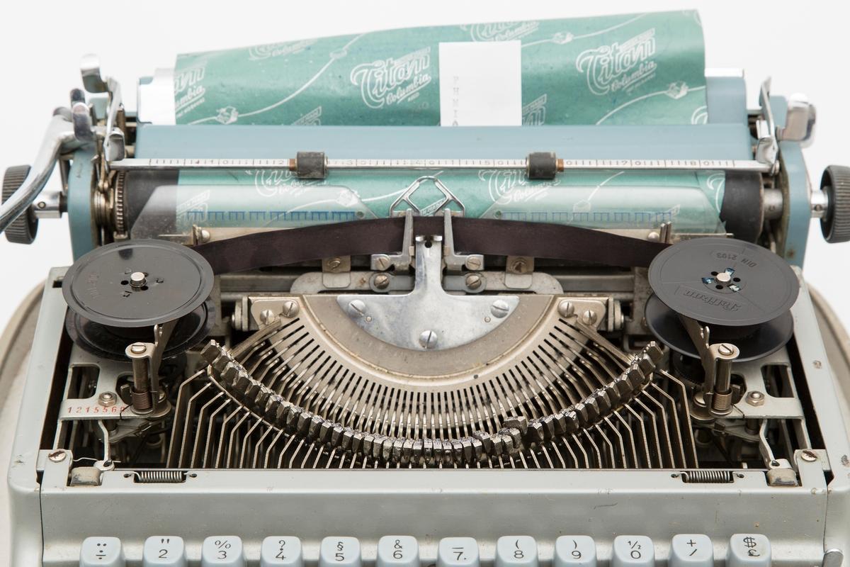 Transportabel skrivemaskin i metall og plast. Skrivemaskinen er fastmontert i koffertbunnen, men kan løftes av. Har avtagbart lokk med bærehåndtak. Transportabel, men relativt stor og tung. En nøkkel følger med.