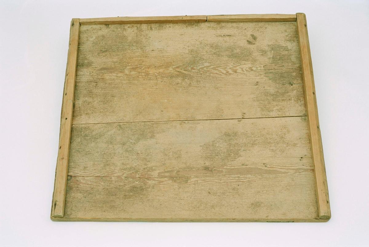 Skiva av två furubrädor sammanfogade av två tvärgående naror, gjord till bakbord genom att lister fastspikats på tre sidor.